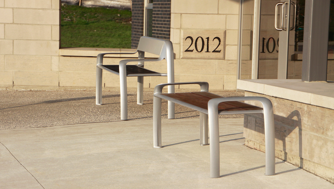 One bench with a back and one without outside a building