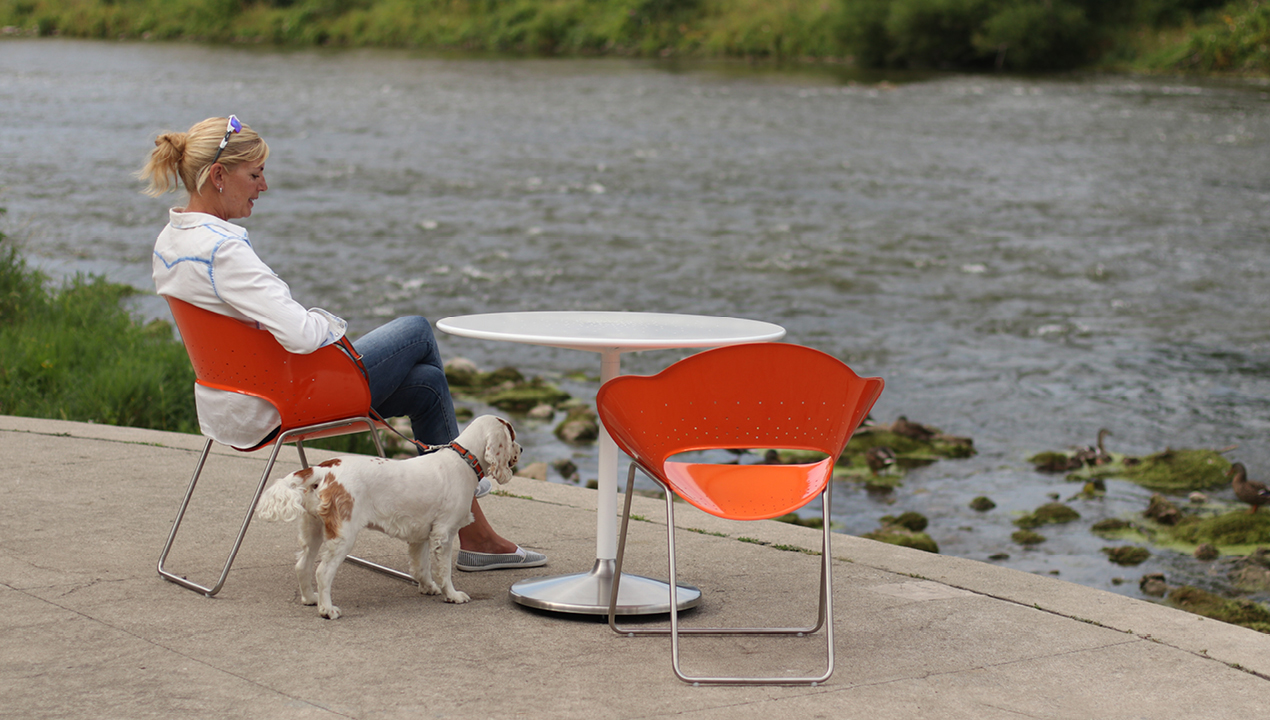 Woman and Dog sitting on Orange Battery Collection Chairs facing the river