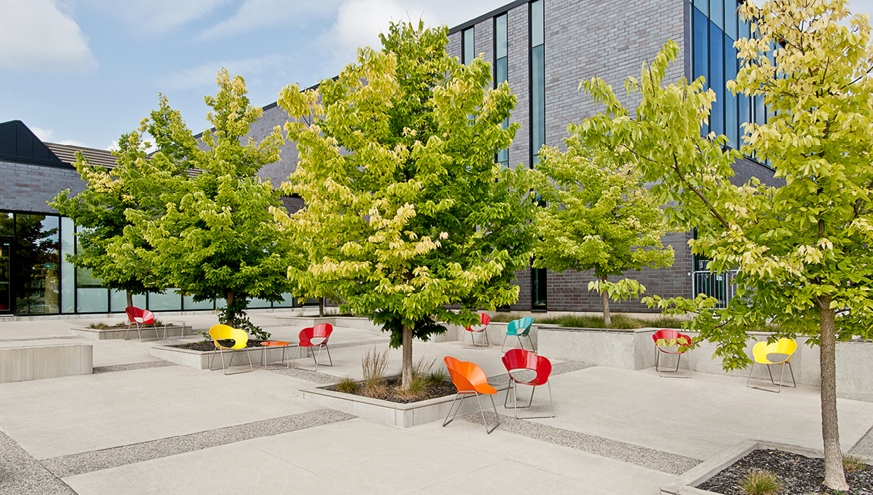 Red, Blue, Yellow and Orange chairs outside building