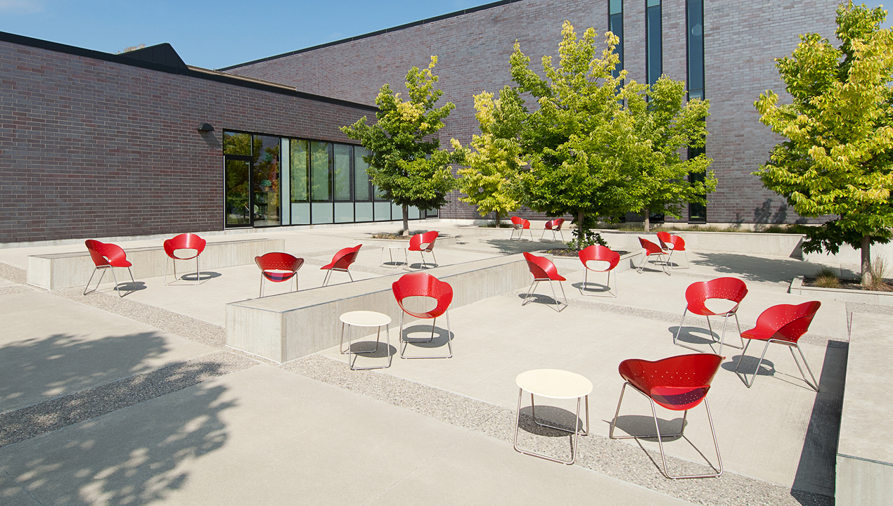 Red Battery Lounge Chairs beside White Tables Outside of Building