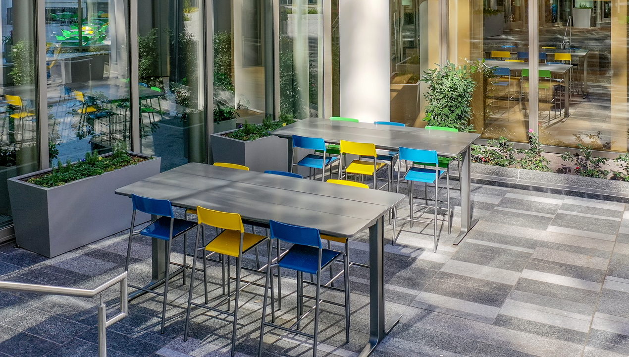 Blue and yellow bar height stools with ancora tables at Bank of America plaza