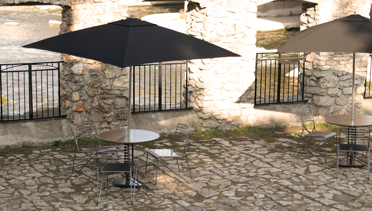 Three Metal Chairs with Round Table with an Attached Black Umbrella
