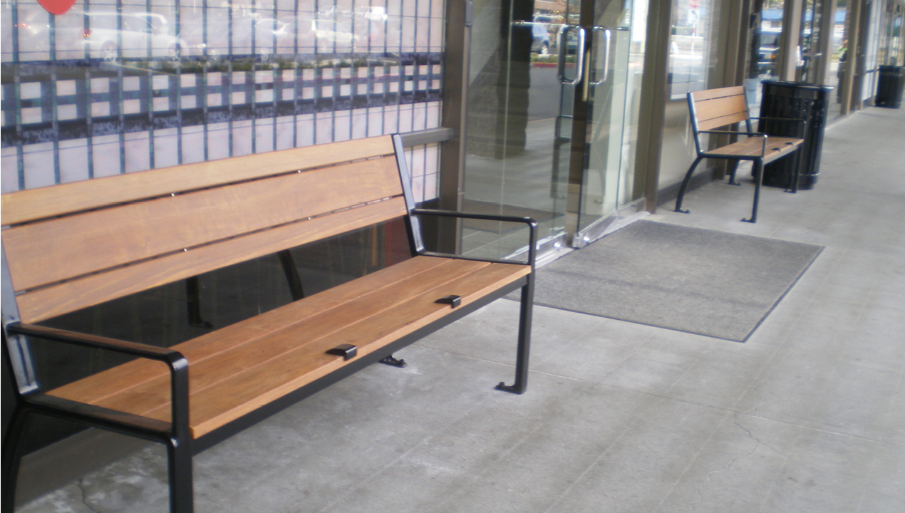 Two wood benches outside entrance to building