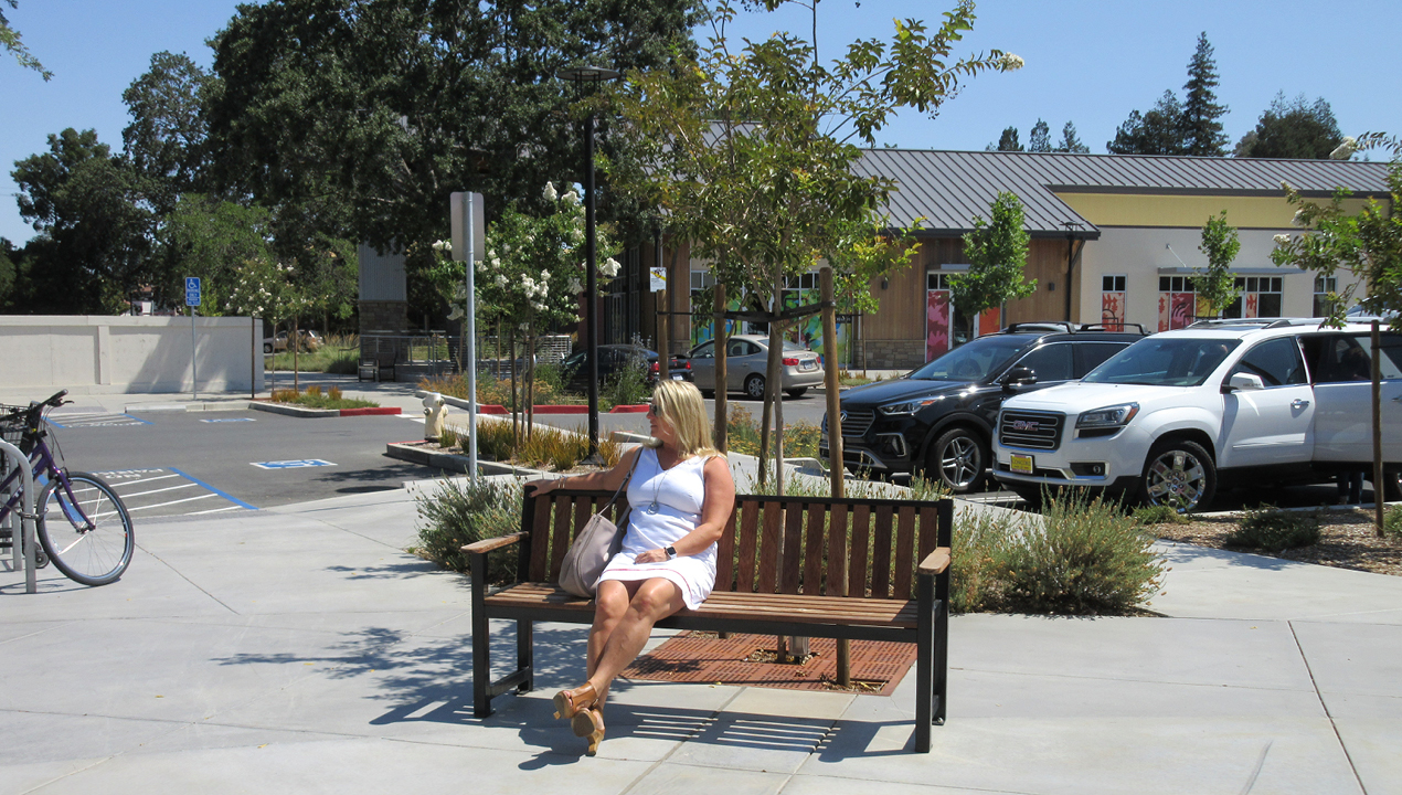 Woman in white sitting on backed bench