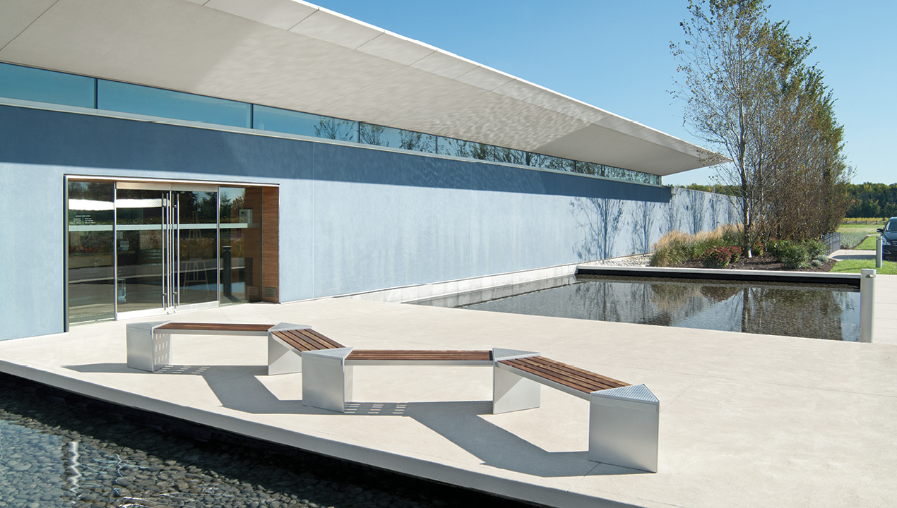 Zig zag Lexicon benches with triangular modules in front of blue building and water