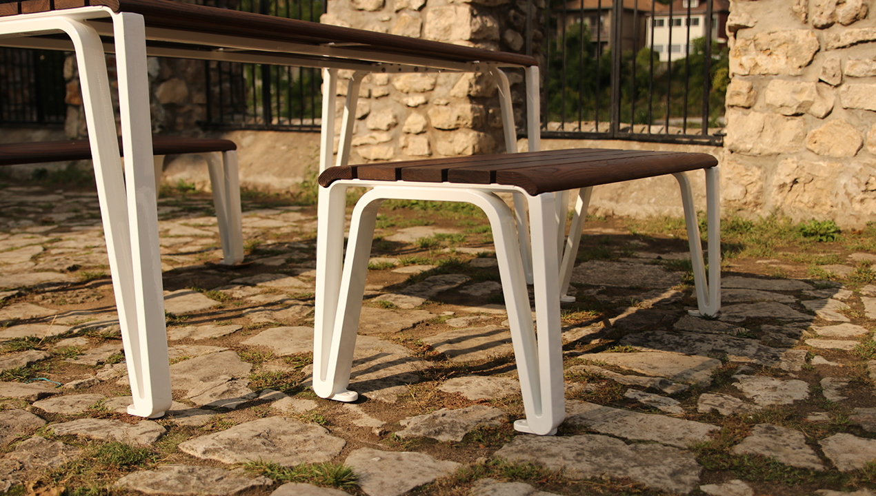 Wood and white backless bench near stone area