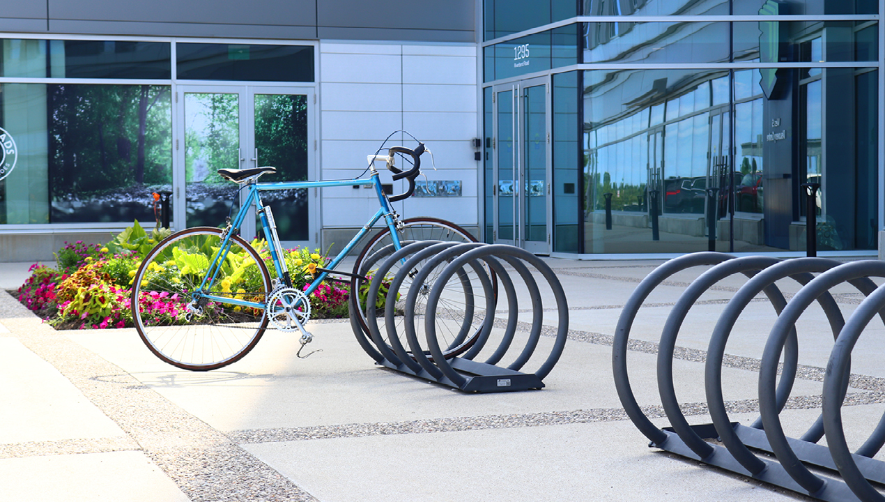 Grey Bike Rack with one bike outside of building