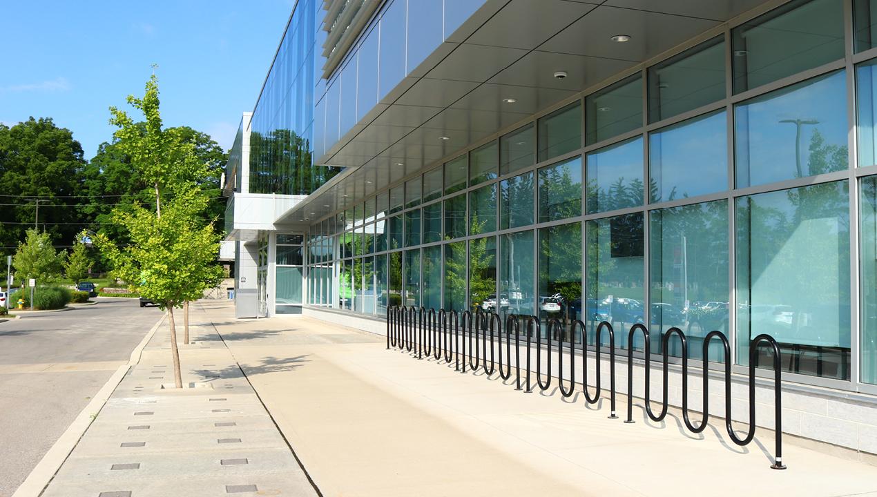Multiple Black Bike Rack's side by side outside building