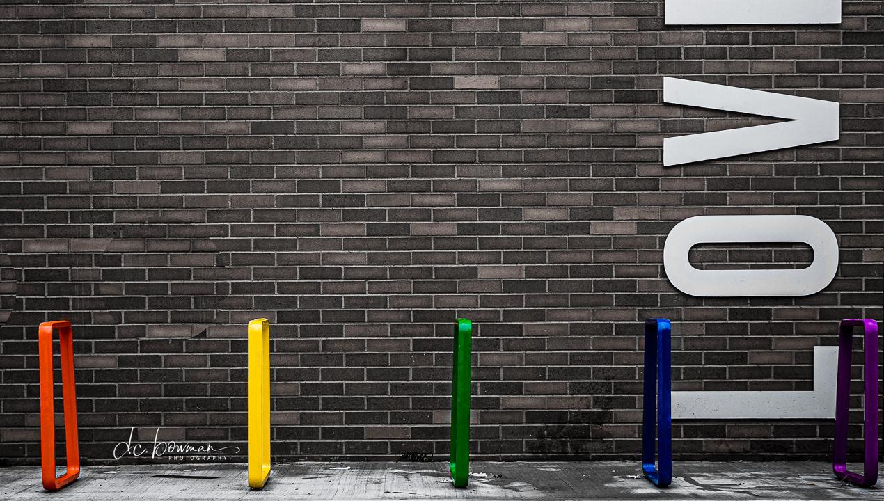 "Bright Coloured Bike Racks near brick wall that says ""LOVE"""