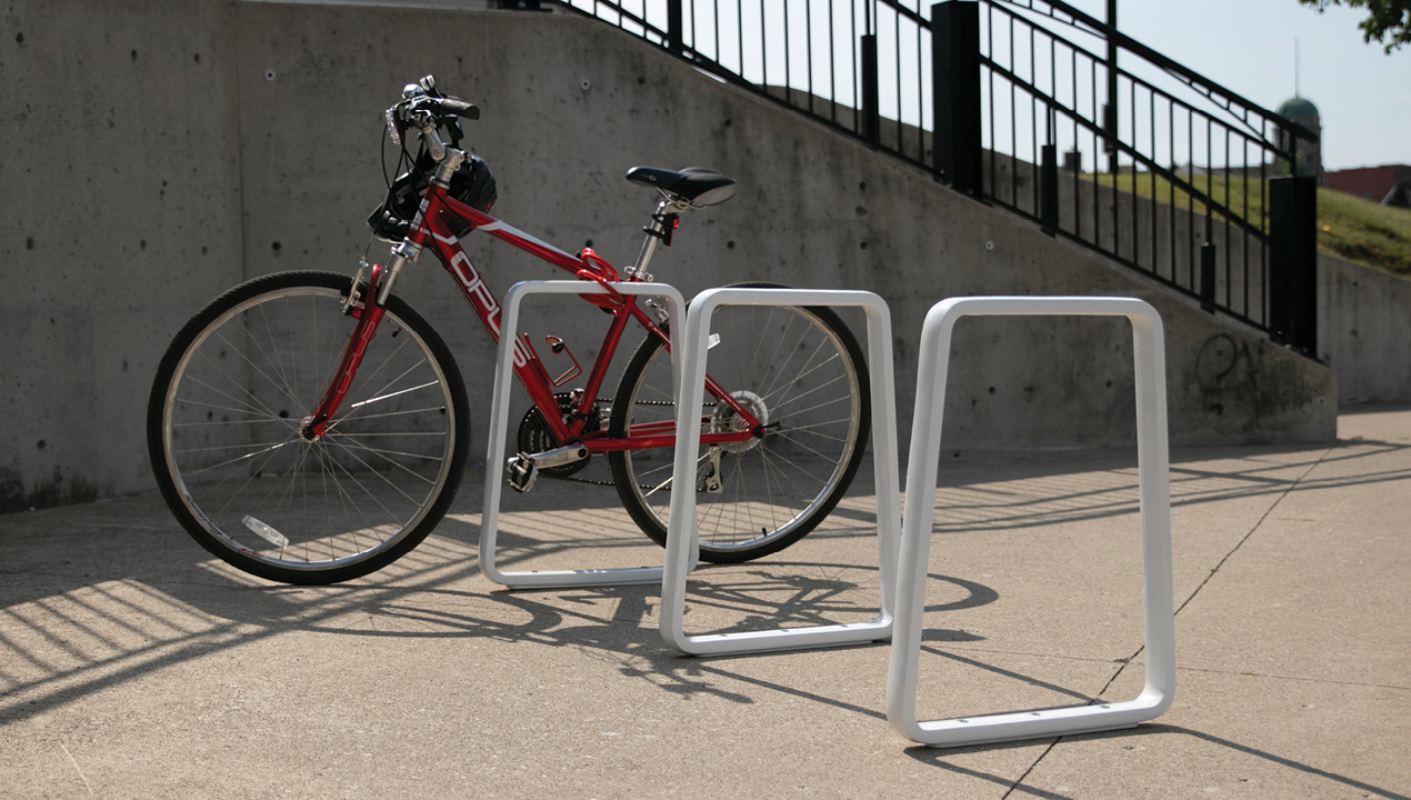 White Bike Rack with Red Bike Leaning on it