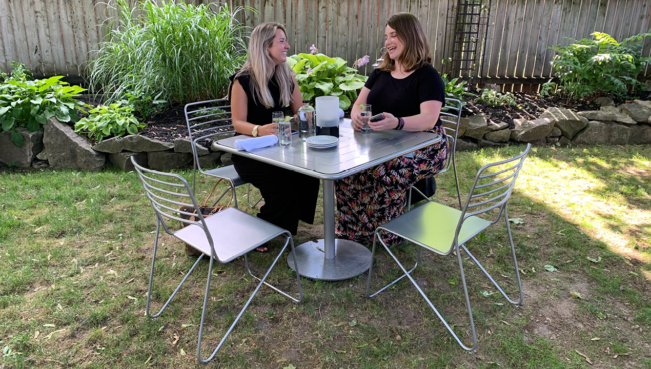 Two women sitting at metal Patio table in a backyard setting