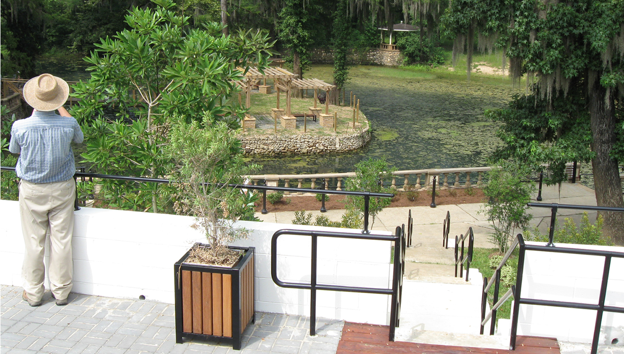 Man Overlooking Garden and Water Area