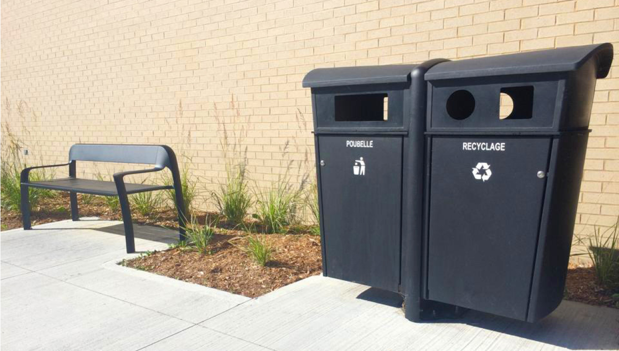 Garbage and Recycling Bins Outside Building Near Gardens and Bench