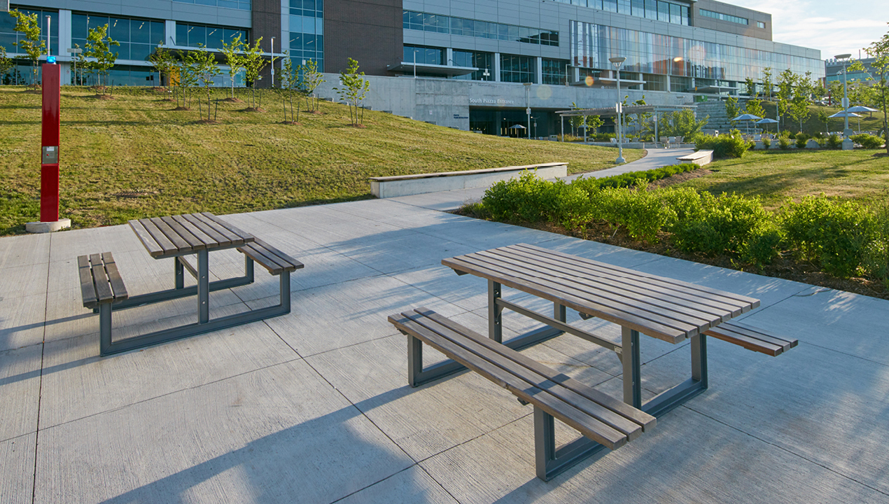 Grey Picnic Tables on Concrete Pads Outside of Building