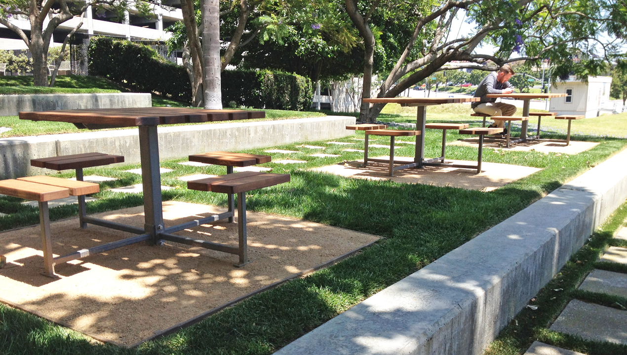 Three wooden tables with individual seatings outside on greens area