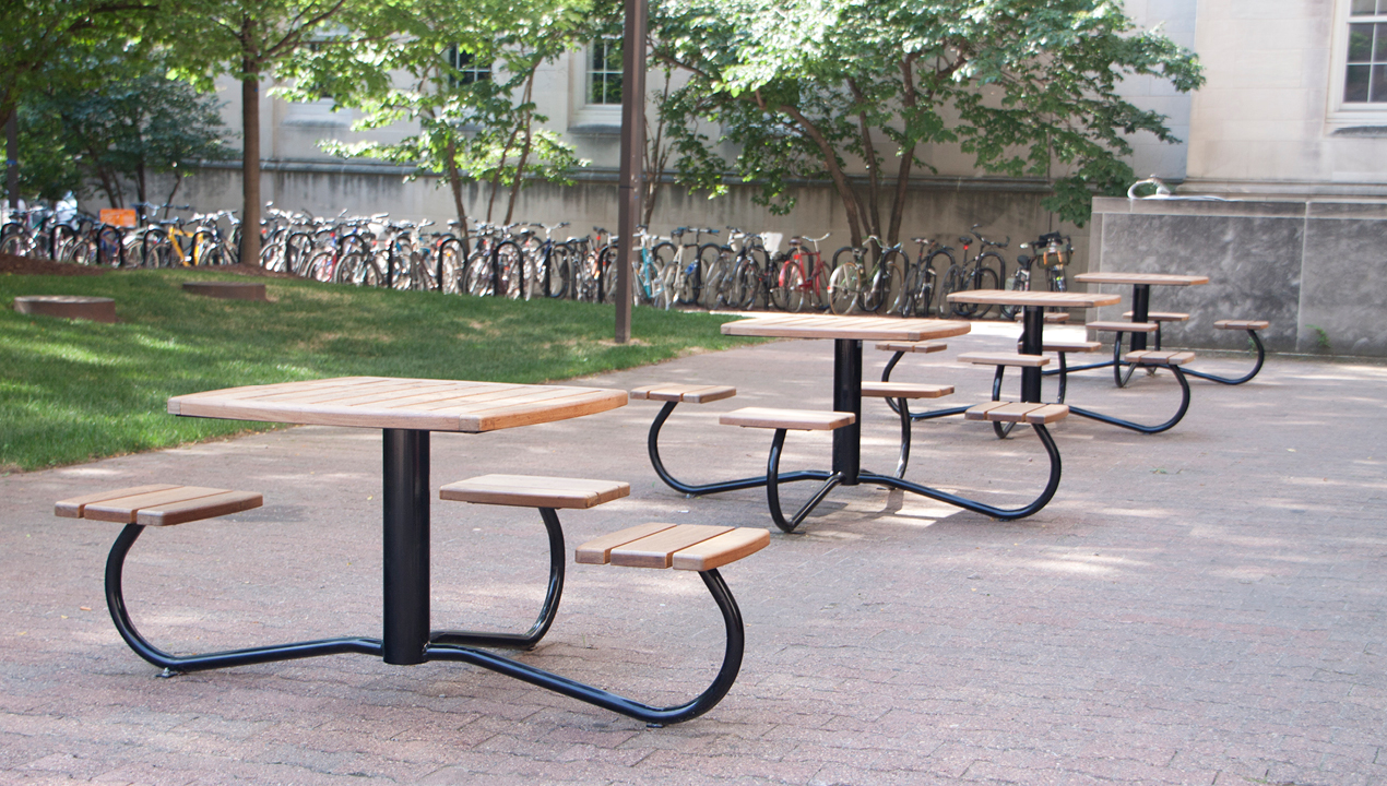 Multiple Tables with Individual Backless Seats outside near a Bike Rack