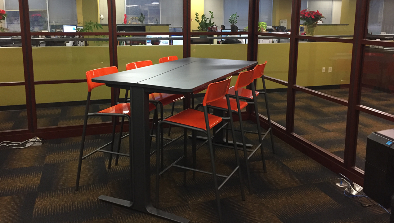 Table inside office with six orange chairs
