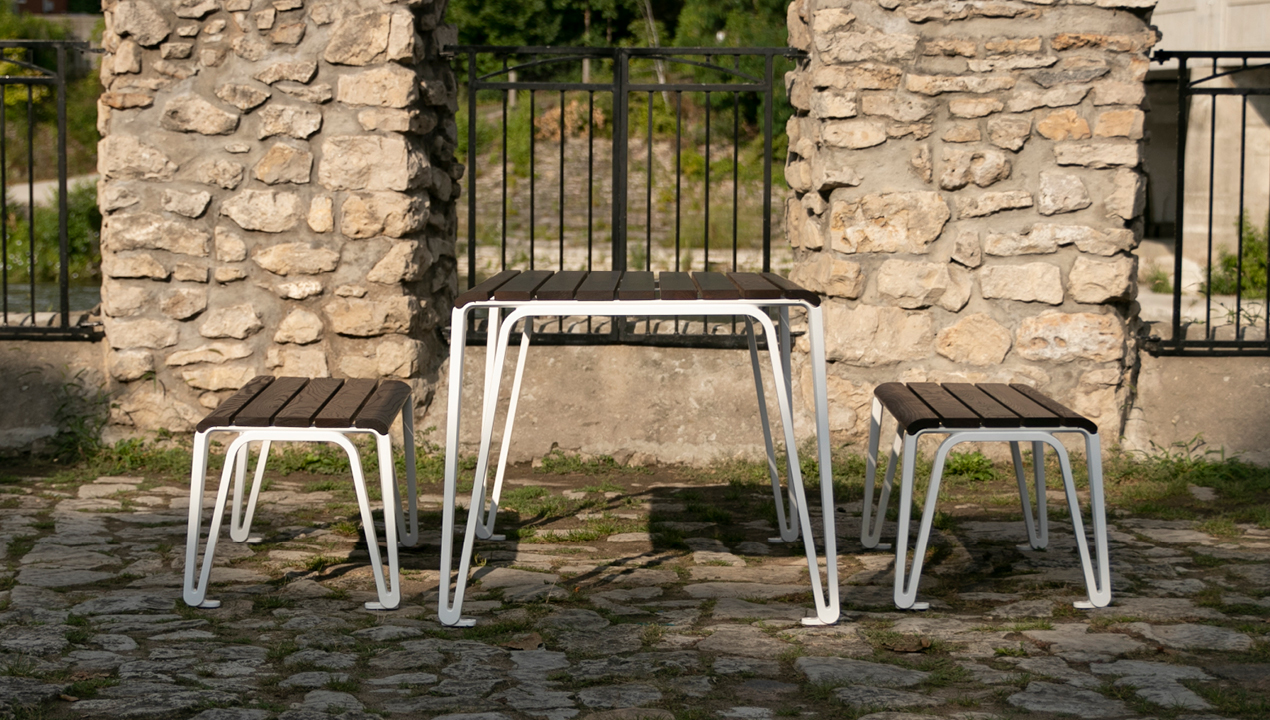 2300 Series Iconic Table and Benches Near Stone Fence