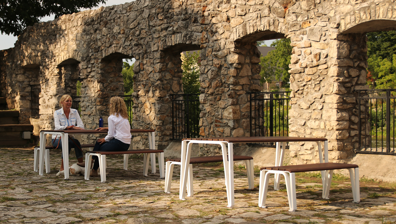 Two women sitting at ICONIC table and benches outside near a stone wall