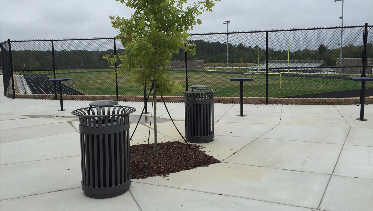 Two Trash Cans Outside a Sports Field