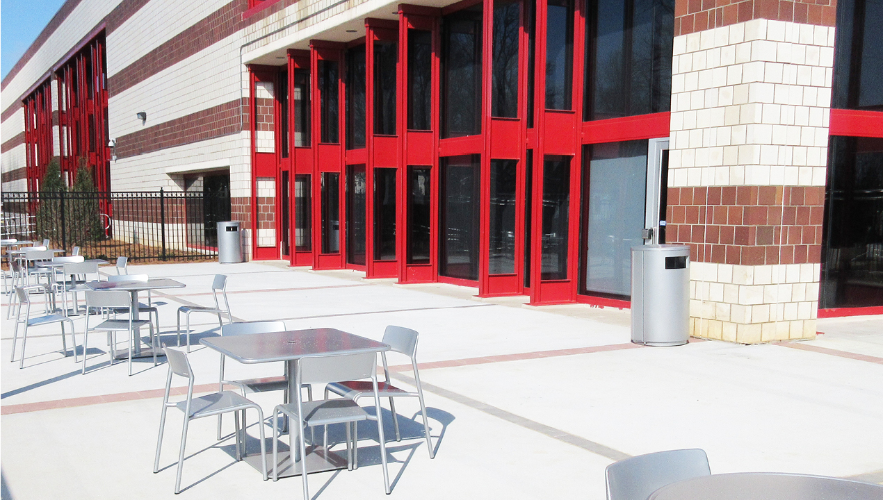 Metal Chairs and Table Outside Red and White Brick Building