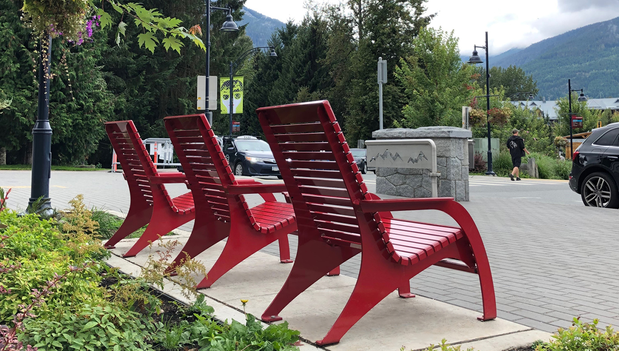 Three red 720 lounge chairs facing the mountains in Whistler