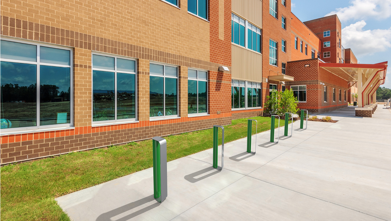 MUG Bike Racks painted gloss green and gunmetal in front of school  building