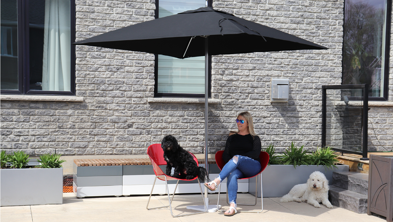 Jill Roberts sitting on battery chairs being shaded by a Tuuci Umbrella