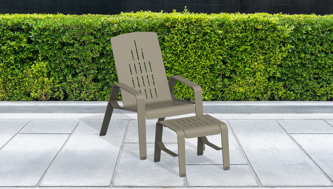 2700 Series - ALUM Lounge Chair and Footrest painted FineTex Titanium in front of green hedges