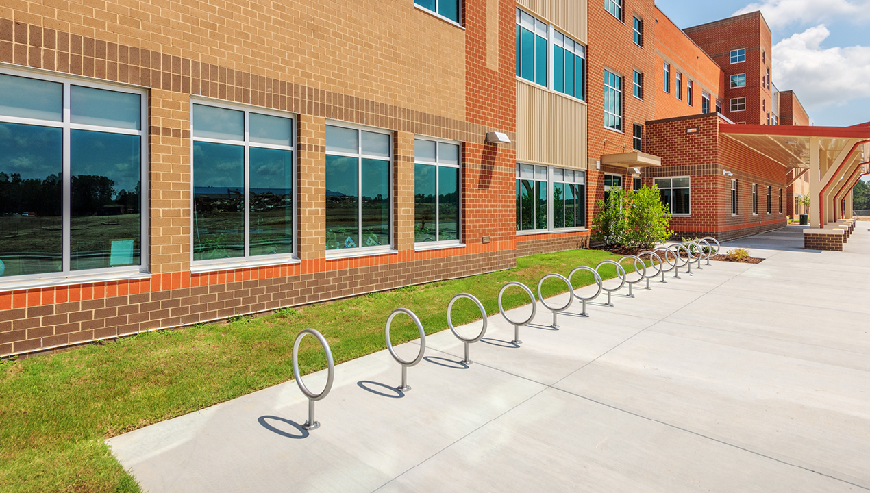 100 Series - 150 Bike Rack lined up in front of school building on bright day