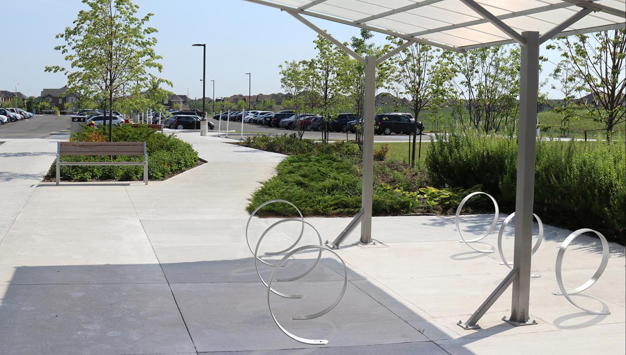 3100 Series - Orbit Stainless Steel Bike Racks under shade, next to gardens