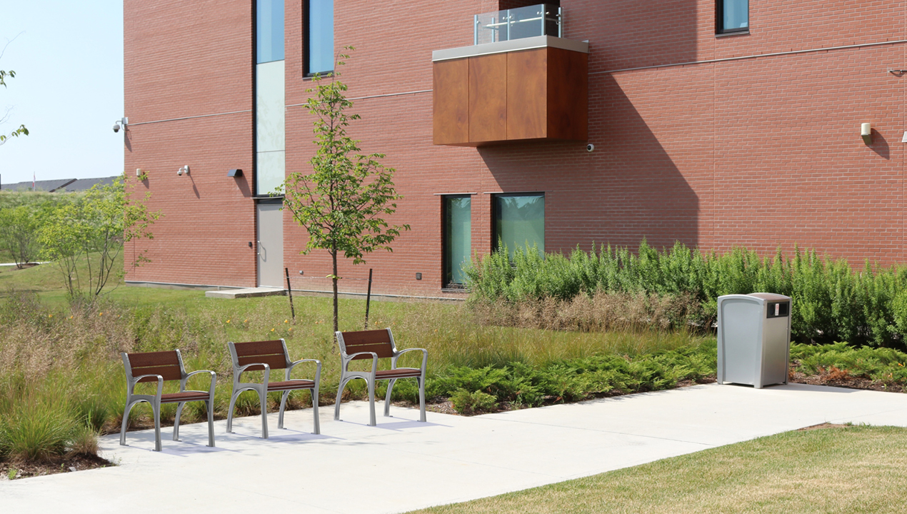 870 Chair in Ipe Wood with greenery next to brick building and 1400 recycle container
