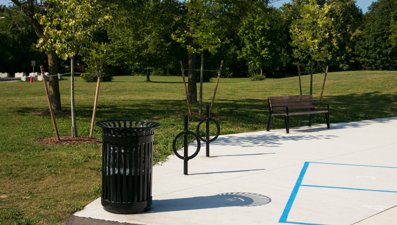 200 Series Trash Receptacle with bike racks and Iconic bench at park